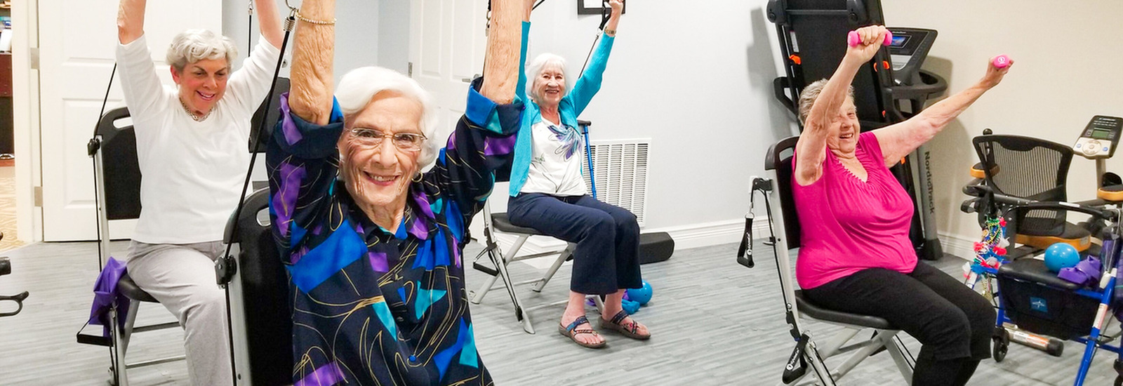 Four older women exercising in chairs